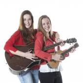 Two teenage sisters play ukelele and guitar in studio — Stock Photo