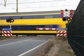 Double deck passenger train at railroad crossing — Stock Photo