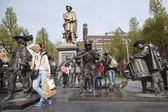 Tourist poses with bronze night watch by rembrandt on square in — Stock Photo