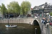 Young people sit on bridge over amsterdam canal while small boat — Stock Photo