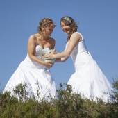Two brides with rugby ball against blue sky background — Stock Photo