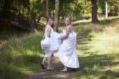 Two brides walk on forest path with skirts in their arms — Stock Photo