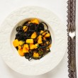 Black spaghetti with pumpkin and garlic sauce — Stock Photo #56953691