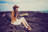 Girl sitting on the rocks on the ocean shore — Stock Photo
