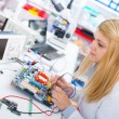Girl with a tester and a printed circuit board — Stock Photo #59029415