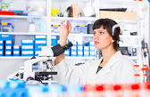 Woman in a laboratory microscope with microscope slide in hand — Stock Photo