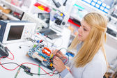 Girl with a tester and a printed circuit board — Stock Photo