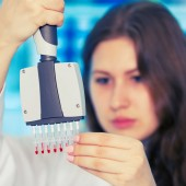 Woman with multi pipette in the laboratory of microbiology — Stock Photo