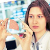 Girl in the laboratory of food quality tests sausage — Stock Photo