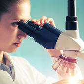Scientist young woman using a microscope in a science laboratory — Stock Photo