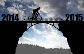 Cyclist riding across the bridge at sunset — Stockfoto