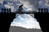 Cyclist riding across the bridge at sunset — Stok fotoğraf
