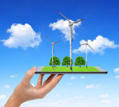 Hand holding digital tablet with a wind turbines and trees — Stock Photo