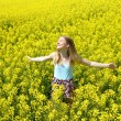 Young happy woman on blooming rapeseed field — Stock Photo #74228319