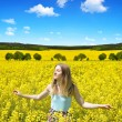 Young happy woman on blooming rapeseed field — Stock Photo #74665331