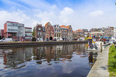 Haarlem, Netherlands, on July 11, 2014. Typical urban view with old buildings on the bank of the channel. Reflection of houses in water — Stock Photo
