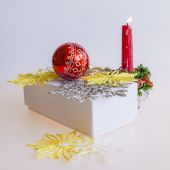 New Year's gift in a white cardboard box, jewelry for a fir-tree and a burning candle — Stock Photo