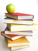 Rough pile of vintage books in multi-colored covers and green apple — Stock Photo