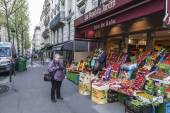 Paris, France, on May 4, 2013. The elderly tourist photographs vegetables and fruit on a counter of the street market — Stock Photo