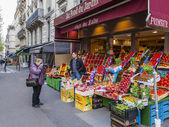 Paris, France, on May 4, 2013. The elderly tourist photographs vegetables and fruit on a counter of the street market — Zdjęcie stockowe