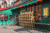 Typical urban view in the early spring morning. Piles of chairs of summer cafe before opening — Stock Photo