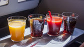 Berlin, Germany, on March 30, 2011. Various drinks in plastic glasses offered in flight to passengers of AirBerlin airline — Photo