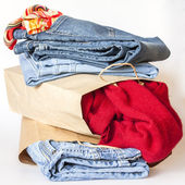 Shopping: a woolen jumper and jeans of various shades in paper packages — Zdjęcie stockowe