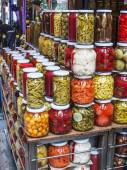 Glass jars with a tinned pickles and marinades on a counter of the market — Stock Photo