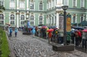 St. Petersburg, Russia, on July 24, 2012. Tourists and citizens stand in the rain in a queue to get to the museum the State Hermitage. The Hermitage - one of the best-known art museums of the world — Foto de Stock