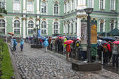 St. Petersburg, Russia, on July 24, 2012. Tourists and citizens stand in the rain in a queue to get to the museum the State Hermitage. The Hermitage - one of the best-known art museums of the world — 图库照片