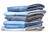 Pile of jeans of various colors on a counter in shop — Stock Photo