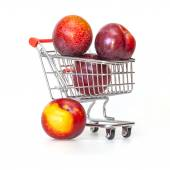 Large red plums in the store cart — Stock Photo