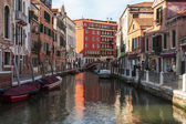 VENICE, ITALY - on APRIL 29, 2015. Typical urban view. Street canal and ancient buildings ashore — Stock Photo