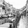 VENICE, ITALY - on APRIL 30, 2015. A typical urban view in rainy weather. Street canal and ancient buildings ashore. Black-and-white image — Stock Photo #73319521