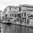 VENICE, ITALY - on APRIL 30, 2015. A typical urban view in rainy weather. Street canal and ancient buildings ashore. Black-and-white image — Stock Photo #73319583