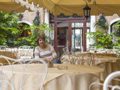 ヴェネツィア, イタリア - 2015 年 5 月 1 日に。夏のカフェの小さなテーブルに座っている女性 — ストック写真