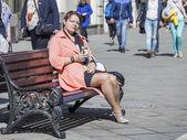 Moscow, Russia, on APRIL 12, 2015. Nikolskaya Street, pedestrian zone. The woman in a bright raincoat has a rest on a bench — Zdjęcie stockowe