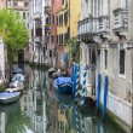 VENICE, ITALY - on MAY 1, 2015. Narrow street canal. Boats are moored near old houses — Stock Photo #76419183