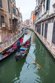 VENICE, ITALY - on MAY 2, 2015. The typical Venetian street canal and its reflection in water. The lonely gondola with passengers floats — Stock Photo