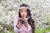 Girl in Pink Ao Dai blowing white cherry petals from her palms — Stock Photo