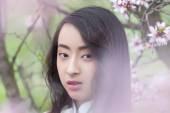 Vietnamese girl in White Ao Dai - almond blossoms — Stock Photo