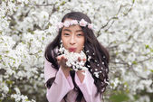 Girl in Pink Ao Dai blowing petals — Stock Photo
