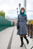 Picture of woman in grey coat walking on causeway — Stock Photo