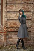 Sad young fashion woman in coat looking back near brick wall — Stock Photo