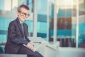 Kid businessman with laptop — Stock Photo