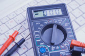 Multimeter on the white laptop. close-up — Stock Photo