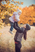 Mother and her baby have fun in the autumn park — Stock fotografie