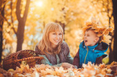 Mother and her kid have fun in the yellow leaves — Foto Stock