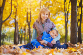 Mother and her kid have fun in the yellow leaves — Stock Photo