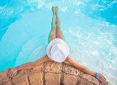 Woman in big hat relaxing on the swimming pool on sunny day. — Stock Photo